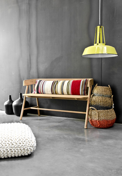 Teak bench with stripey cushion and baskets